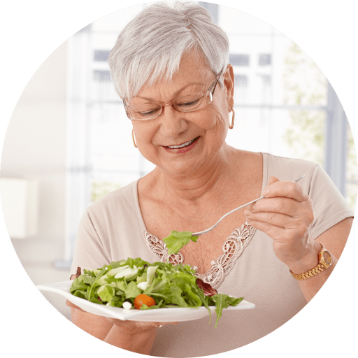 An older woman with dental implants eating a salad