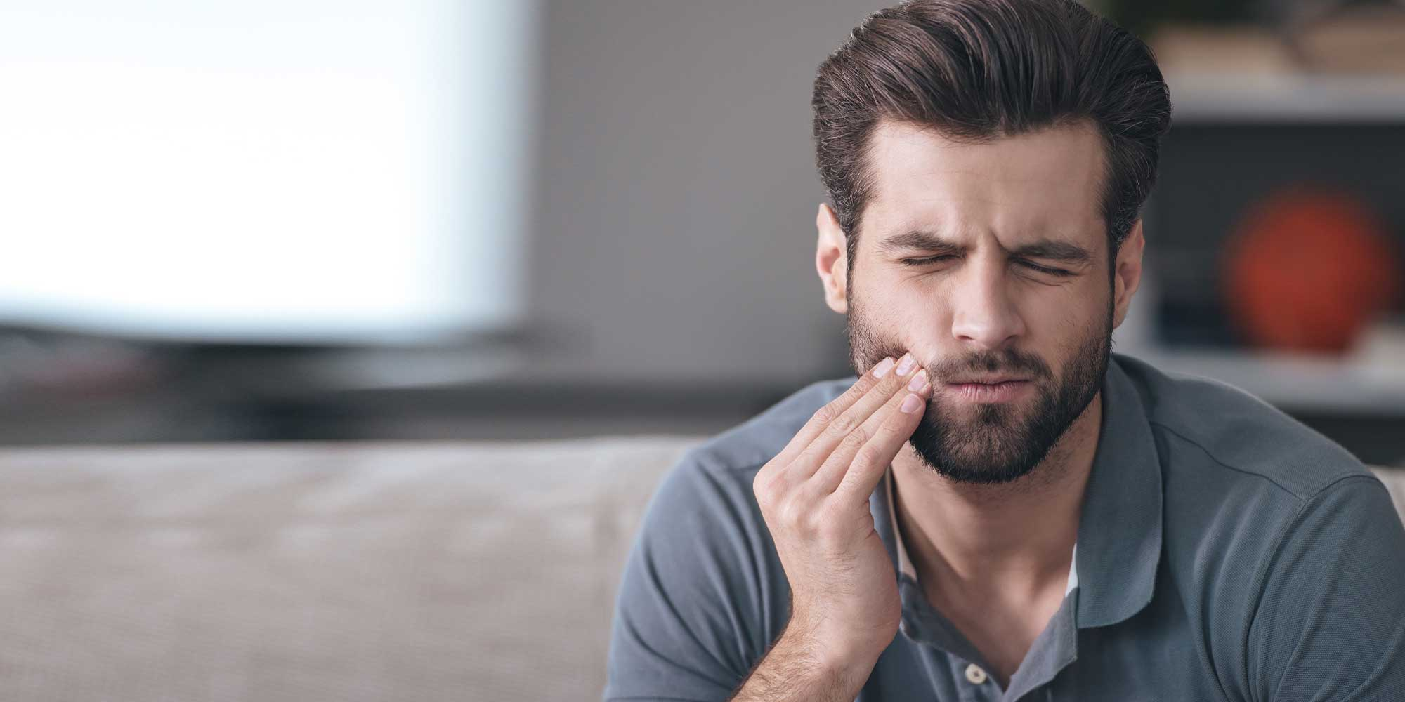 A young man with a beard holding his jaw in pain